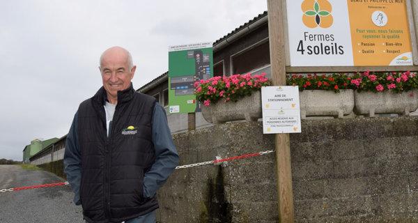Denis Le Mer devant entrée du site avicole avec panneaux et chaîne